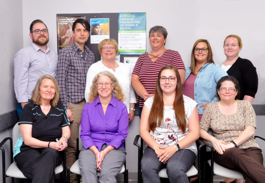 A picture of the members of interdisciplinary health professionals at the ELFHT, arranged in two rows, with 6 of them standing behind 4 others sitting in chairs.